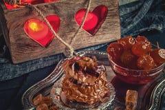 Η ψημένη Apple με τα καρύδια, το μέλι και η Apple φράσσουν για το τσάι στο υπόβαθρο του κατόχου κεριών με τις καρδιές Στοκ Φωτογραφία