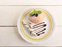 Η ψημένη Apple με τους ρόλους γκοφρετών σε ένα πιάτο με τη σοκολάτα και powde Στοκ Φωτογραφία