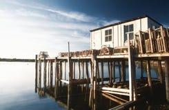 Η ψηφιακά αλλαγμένη, υψηλή άποψη αντίθεσης μιας αποβάθρας συσσώρευσε με τις παγίδες αστακών στο ήρεμο νερό από το νησί ερήμων υπο Στοκ Εικόνα
