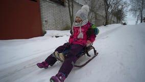 Η ψυχαγωγία των χειμερινών παιδιών, το ευτυχή μικρό παιδί και το κορίτσι οδηγούν σε ένα έλκηθρο κατά μήκος του χιονώδους δρόμου φιλμ μικρού μήκους