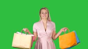 Η ψωνίζοντας ευτυχής χαμογελώντας εκμετάλλευση γυναικών που ψωνίζει τοποθετεί το iwhile περπάτημα σε μια πράσινη οθόνη σε σάκκο,  απόθεμα βίντεο