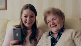 Η όμορφες γιαγιά και η κόρη κάνουν selfie και χαμογελούν καθμένος στον καναπέ στο σπίτι απόθεμα βίντεο