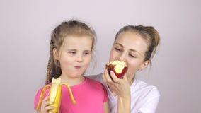 Η όμορφες κόρη και η μητέρα τρώνε τα φρούτα και το χαμόγελο φιλμ μικρού μήκους