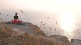 Η όμορφη άποψη της γυναίκας που κάνει τη συνδεδεμένη Konasana γωνία Baddha γιόγκας θέτει στο βουνό με την άποψη θάλασσας στο ηλιο φιλμ μικρού μήκους