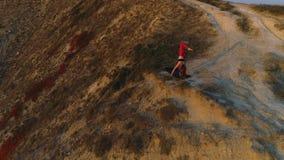 Η όμορφη άποψη της γυναίκας που κάνει το μισό φεγγάρι γιόγκας θέτει, Ardha Chandrasana, στο βουνό στο ηλιοβασίλεμα φιλμ μικρού μήκους