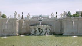 Η όμορφη άσπρη μπαρόκ πηγή ύφους με τα αγάλματα των ανθρώπων, ροές του νερού χύνει φιλμ μικρού μήκους