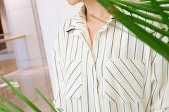 Η όμορφη άσπρη ριγωτή μόδα πουκάμισων μπλουζών γυναικών απαριθμεί κοντά επάνω ελάχιστο άνετο καθιερώνον τη μόδα ύφος μόδας Στοκ Φωτογραφίες