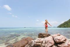 Η όμορφη άσπρη τρίχα κοριτσιών και το κόκκινο swimmingsuit που μένουν στην παραλία βράχου, χαλαρώνοντας και απολαμβάνουν της ελευ Στοκ Φωτογραφία