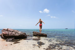 Η όμορφη άσπρη τρίχα κοριτσιών και το κόκκινο swimmingsuit που μένουν στην παραλία βράχου, χαλαρώνοντας και απολαμβάνουν της ελευ Στοκ Εικόνες