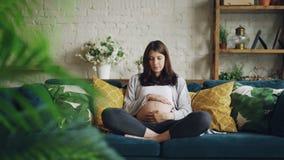 Η όμορφη έγκυος νέα γυναίκα brunette κτυπά τη tummy σκέψη της για τη συνεδρίαση μωρών στον καναπέ στο σύγχρονο διαμέρισμα φιλμ μικρού μήκους