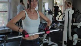 Η όμορφη αθλητική γυναίκα εκτελεί έναν ανελκυστήρα στο πηγούνι στη γυμναστική απόθεμα βίντεο