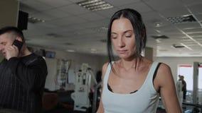 Η όμορφη αθλητική γυναίκα και ένας άνδρας με το υπερβολικό βάρος εκπαιδεύουν treadmill φιλμ μικρού μήκους