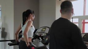 Η όμορφη αθλητική γυναίκα και ένας άνδρας με το υπερβολικό βάρος εκπαιδεύουν treadmill απόθεμα βίντεο