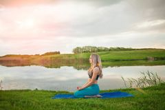 Η όμορφη αθλητική ξανθή γιόγκα άσκησης κοριτσιών στη λίμνη στο ηλιοβασίλεμα, κινηματογράφηση σε πρώτο πλάνο, αυτό υποστηρίζει ένα Στοκ Φωτογραφίες