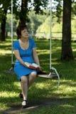 Η όμορφη ανώτερη γυναίκα στο μπλε φόρεμα σημείων Πόλκα κάθεται Στοκ Εικόνες