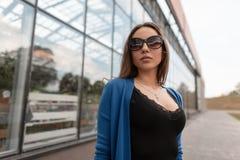 Η όμορφη αρκετά προκλητική νέα γυναίκα hipster στα μοντέρνα γυαλιά ηλίου σε ένα πλεκτό ακρωτήριο σε μια μπλούζα με τη δαντέλλα στ στοκ εικόνες