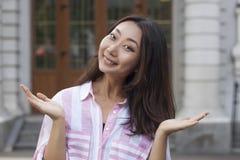 Η όμορφη ασιατική γυναίκα ευτυχώς και έκπληκτος παρουσιάζει δάχτυλα με ένα χαμόγελο στοκ φωτογραφία