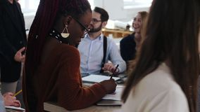 Η όμορφη αφρικανική νέα γυναίκα εργάζεται με τα έγγραφα στο lap-top, ευτυχείς multiethnic επιχειρηματίες στο υπόβαθρο γραφείων φιλμ μικρού μήκους