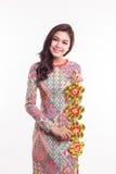 Η όμορφη βιετναμέζικη γυναίκα που φορά το dai AO εντύπωσης που κρατά τυχερό διακοσμεί το αντικείμενο στοκ φωτογραφία με δικαίωμα ελεύθερης χρήσης