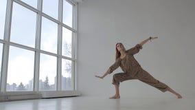 Η όμορφη γιόγκα άσκησης γυναικών γιόγκας και στάση στη δευτερεύουσα γωνία θέτει φιλμ μικρού μήκους