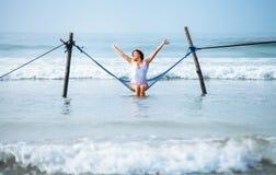 Η όμορφη γυναίκα απολαμβάνει με το ωκεάνιο αεράκι και ο ήλιος κάθεται στο swi αιωρών Στοκ Φωτογραφία