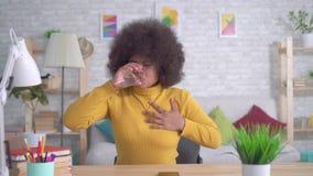 Η όμορφη γυναίκα αφροαμερικάνων με έναν πόνο επίθεσης ή καρδιών afro hairstyle απροσδόκητο παίρνει ένα χάπι απόθεμα βίντεο