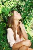 Η όμορφη γυναίκα εισπνέει το άρωμα των άσπρων λουλουδιών στοκ εικόνες με δικαίωμα ελεύθερης χρήσης