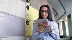 Η όμορφη γυναίκα εξετάζει στην ταμπλέτα και έκπληκτος σε κάτι το γραφείο απόθεμα βίντεο