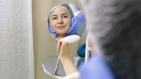 Η όμορφη γυναίκα εξετάζει την στον καθρέφτη μετά από τις καλλυντικές διαδικασίες στο σαλόνι ομορφιάς φιλμ μικρού μήκους