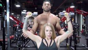 Η όμορφη γυναίκα ικανότητας και ο νέος άνδρας εκπαιδευτών ασκούν τους μυς με την ανύψωση των όπλων με τους αλτήρες στη γυμναστική απόθεμα βίντεο