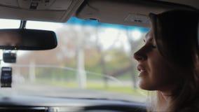 Η όμορφη γυναίκα κάθεται σε ένα αυτοκίνητο Κοιτάζει στο παράθυρο, γυρίζει το κεφάλι της και μιλά στον οδηγό, που ταξιδεύει με το  φιλμ μικρού μήκους