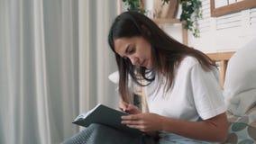 Η όμορφη γυναίκα κάθεται στο κρεβάτι και κάνει τις σημειώσεις στον καθημερινό αρμόδιο για το σχεδιασμό, σε αργή κίνηση απόθεμα βίντεο