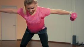 Η όμορφη γυναίκα κάνει την αθλητική άσκηση με τους αλτήρες στο τραμπολίνο στη γυμναστική απόθεμα βίντεο