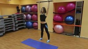 Η όμορφη γυναίκα κάνει τις ασκήσεις με το αθλητικό ραβδί απόθεμα βίντεο
