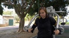 Η όμορφη γυναίκα κάνει excercises για τα χέρια στον εξοπλισμό οδών στοκ φωτογραφία με δικαίωμα ελεύθερης χρήσης