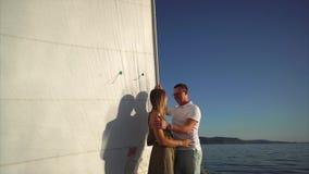 Η όμορφη γυναίκα και ο όμορφος άνδρας στέκονται σε ένα γιοτ, που επιπλέει στη θάλασσα απόθεμα βίντεο
