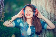 Η όμορφη γυναίκα κοντά στο δέντρο και τον τομέα lupine ακούει τη μουσική στα ακουστικά και έχει τη διασκέδαση στοκ φωτογραφίες