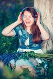 Η όμορφη γυναίκα κοντά στο δέντρο και τον τομέα lupine ακούει τη μουσική στα ακουστικά και έχει τη διασκέδαση στοκ φωτογραφία με δικαίωμα ελεύθερης χρήσης