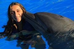 Η όμορφη γυναίκα κοριτσιών που φιλά ένα πανέμορφο δελφινιών ευτυχές παιδί προσώπου βατραχοπέδιλων χαμογελώντας κολυμπά τα δελφίνι στοκ φωτογραφία