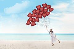 Η όμορφη γυναίκα κρατά τα μπαλόνια καρδιών στοκ φωτογραφίες