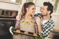 Η όμορφη γυναίκα κρατά το καυτό ψήνοντας τηγάνι με τα μπισκότα, και εξετάζει τον ευτυχή σύζυγό της στοκ φωτογραφία