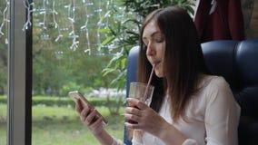 Η όμορφη γυναίκα με ένα τηλέφωνο σε έναν καφέ ανακατώνει το θερμαμένο κρασί φιλμ μικρού μήκους