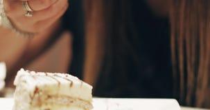 Η όμορφη γυναίκα με μακρυμάλλη τρώει ένα εύγευστο κέικ σε ένα εστιατόριο φιλμ μικρού μήκους