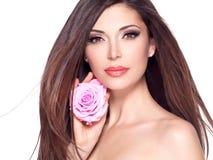 Η όμορφη γυναίκα με μακρυμάλλη και αυξήθηκε στο πρόσωπο στοκ φωτογραφία