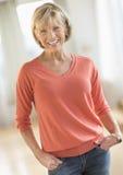 Η όμορφη γυναίκα με παραδίδει τις τσέπες που στέκονται στο σπίτι Στοκ Εικόνες