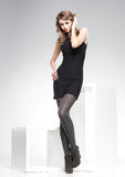 Η όμορφη γυναίκα με τα μακριά προκλητικά πόδια έντυσε την κομψή τοποθέτηση στο στούντιο Στοκ εικόνες με δικαίωμα ελεύθερης χρήσης