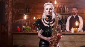 Η όμορφη γυναίκα με τα μοντέρνα μαύρα σκηνικά ενδύματα τραγουδά σε ένα saxophone φιλμ μικρού μήκους