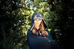 Η όμορφη γυναίκα με τα μπλε μάτια, τη μακροχρόνιες καφετιές τρίχα και την κουκούλα φορά μια μάσκα όπως τα μπλε μάτια εξετάζουν τη στοκ εικόνα