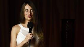 Η όμορφη γυναίκα με την όμορφη μακριά κυματιστή τρίχα κρατά mic και τραγουδά με το φωτεινό χαμόγελο απόθεμα βίντεο