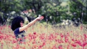 Η όμορφη γυναίκα με την παπαρούνα ανθίζει την άνοιξη απόθεμα βίντεο